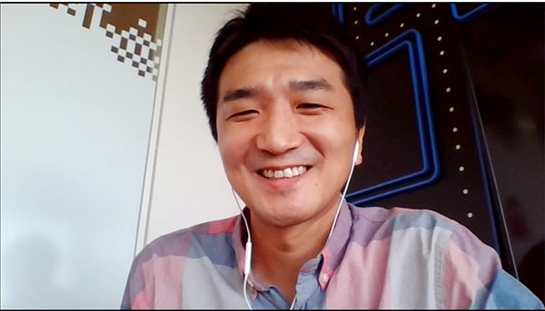 Kubota sits in front of a wall decorated with a PAC-MAN maze during the video call interview.